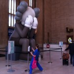 A person in blue leans back to take a photo of COMPANION art installation by KAWS at 30th Street Station