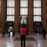 A person in red takes a photo of COMPANION art installation by KAWS at 30th Street Station