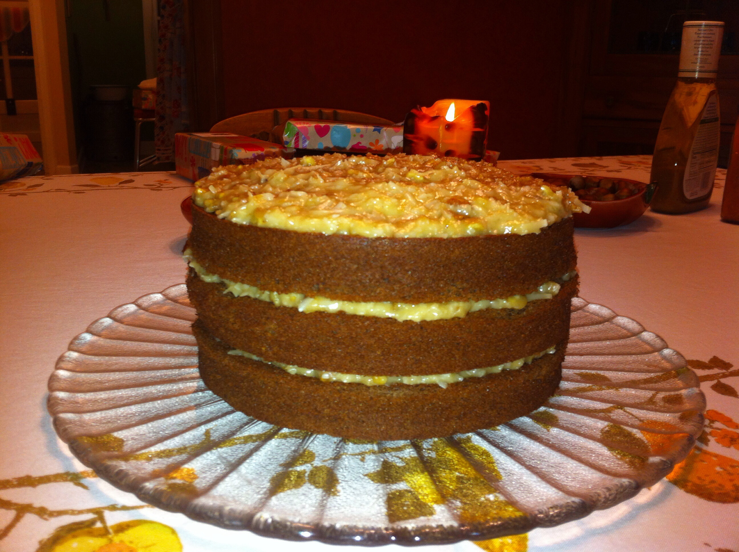 A not so great iPhone shot of the cake on a platter with coconut-pecan frosting showing between layers
